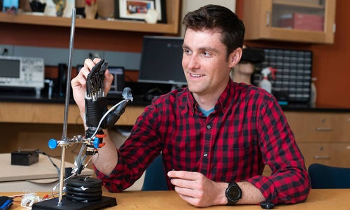 Luke Osborn, graduate student, interacting with a prosthetic hand covered in the e-dermis
